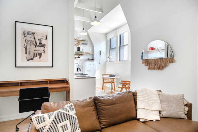 living room with leather sofa and eat in kitchen in background of River North Chicago loft apartment for rent