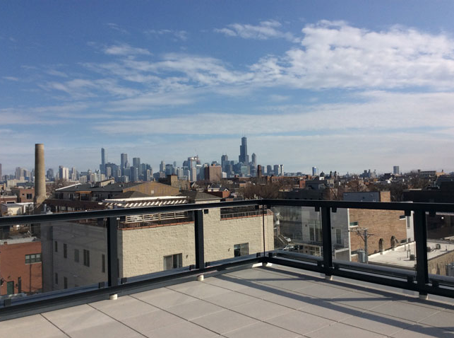 Large rooftop deck with city views of Chicago and glass panel railings