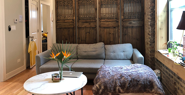 gray sofa with coffee table in front and antique wooden room dividers behind it in Chicago apartment for rent