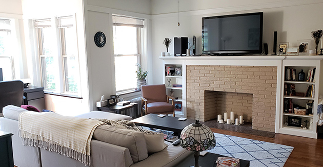 fireplace mantel with TV mounted above and sofa in front of it in living room of Chicago apartment for rent