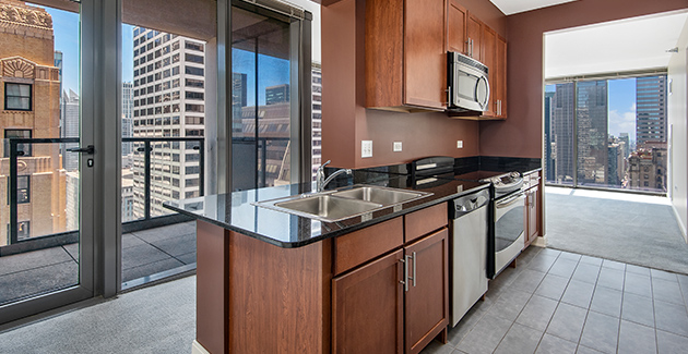 kitchen with open concept living room and floor-to-ceiling windows in Loop apartment for rent, Chicago