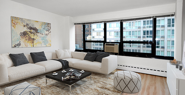 living room with white sectional sofa and windows in Lakeview apartment for rent