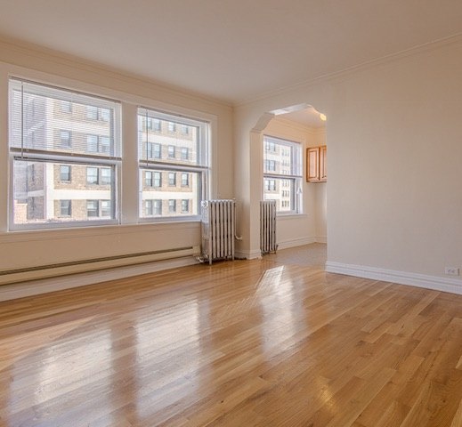 living room with hardwood flooring and arched doorways in Lakeview Chicago apartment for rent