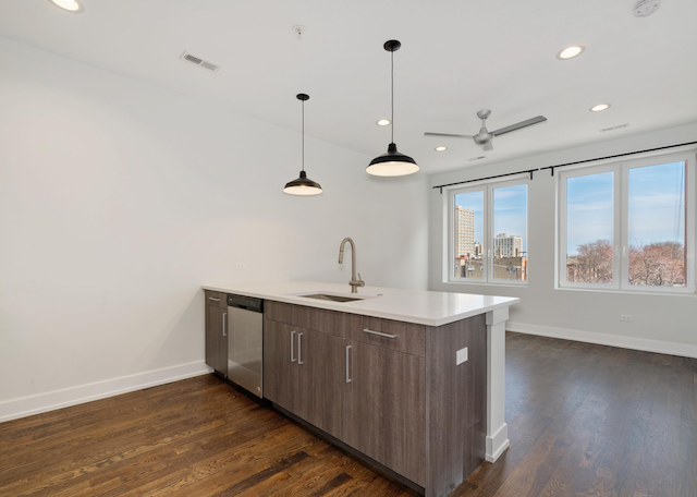 kitchen island with hanging pendant lights and living area behind it in 1 bedroom apartment for rent in Uptown Chicago