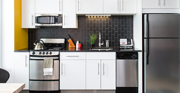 kitchen with stainless steel appliances, black tile backsplash and white cabinets in apartment for rent in Chicago