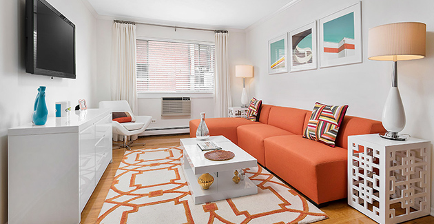 living room with orange decor accents and white coffee table in 515 W Barry Apartments in Lakeview Chicago