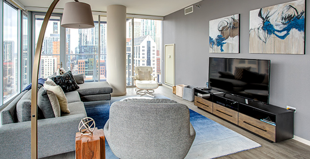 grey sofa and armchair facing a flat screen TV in the living room of a luxury apartment for rent in Chicago