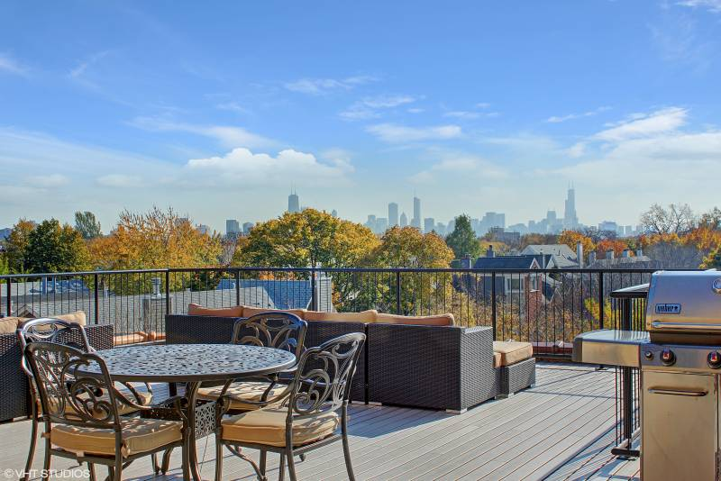 Modern rooftop deck with city views of Chicago, wicker patio furniture, and black metal railing