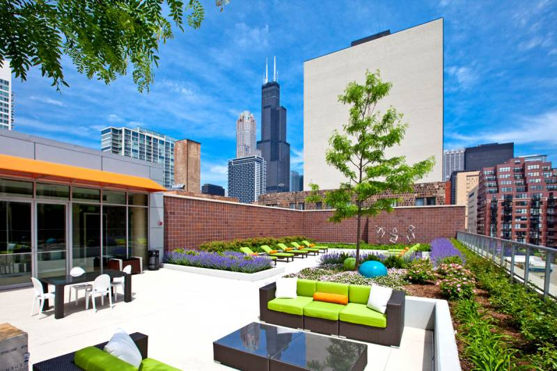 Modern rooftop deck with city views of downtown Chicago, bright colored patio furniture and lounge chairs