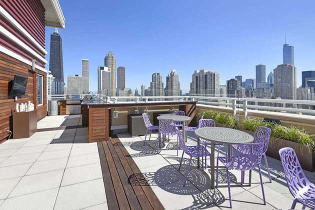 Modern rooftop deck with city views of Chicago, purple patio furniture, stainless steel grill, and outdoor tv