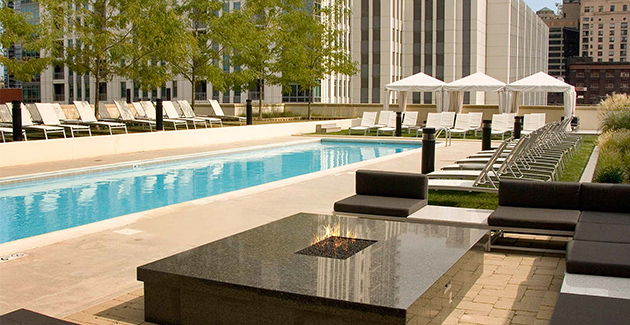 outdoor swimming pool surrounded by lounge furniture and a fire pit at Fulton Market apartment building Echelon Chicago