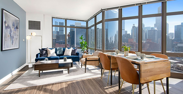 the dining area with wooden dining table and living room behind it in a luxury apartment for rent in Fulton Market neighborhood of Chicago