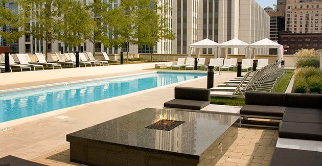 fire pit and lounge beside swimming pool on rooftop terrace of Fulton Market apartment building Echelon Chicago