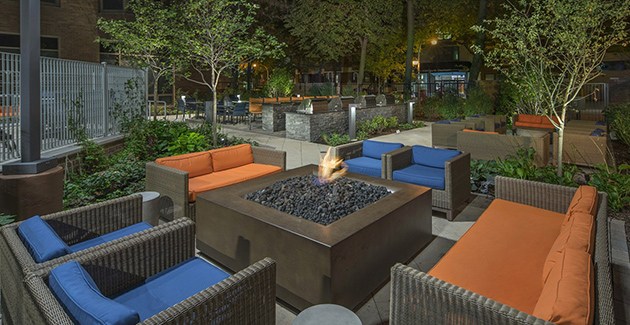 outdoor furniture surrounding fire pit in patio of Gold Coast apartments at Elm Street Plaza
