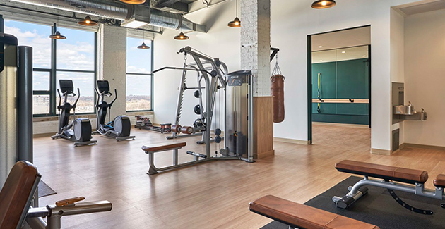 fitness center with large factory windows and high ceilings at Fields Lofts in Chicago
