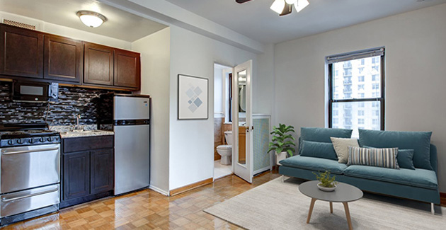 studio apartment with blue sofa and white area rug in Old Town, Chicago