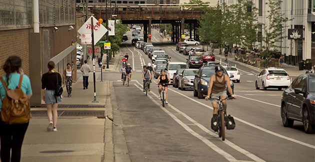 cyclists riding northwest on North Milwaukee Avenue in the Fulton Market neighborhood of Chicago