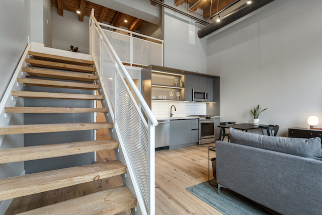 living room with staircase leading up to bedroom in loft apartment for rent in River West Chicago
