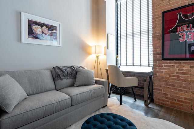 a Chicago loft apartment with exposed brick walls and convenient office nook nearby a window in the second bedroom