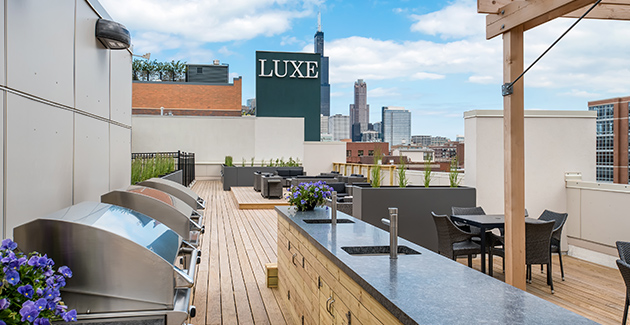 open air patio with grill stations and wet bar on rooftop of Luxe on Madison apartments in West Loop, Chicago
