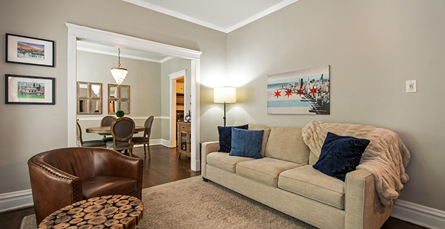 living room of 1 bedroom apartment for rent in Lincoln Park with Chicago flag artwork on wall above sofa