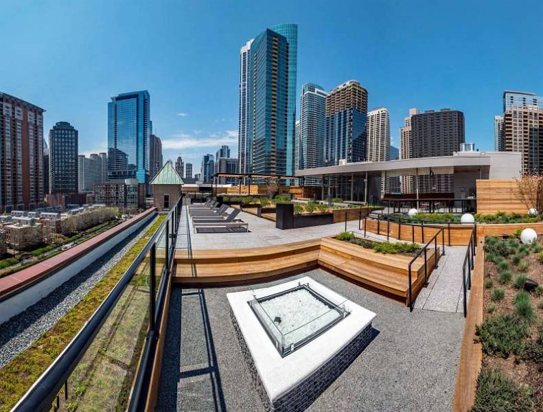 Modern rooftop deck with city views of Chicago, firepits, lounge chairs, and a garden
