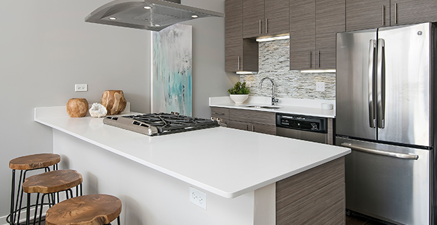 white quartz kitchen counter with breakfast bar seating and range cooker in kitchen of luxury apartment for rent in West Loop, Chicago