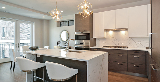 kitchen island with gold pendant lighting above and white marble counter tops in Lakeview apartment for rent in Melrose on the Lake
