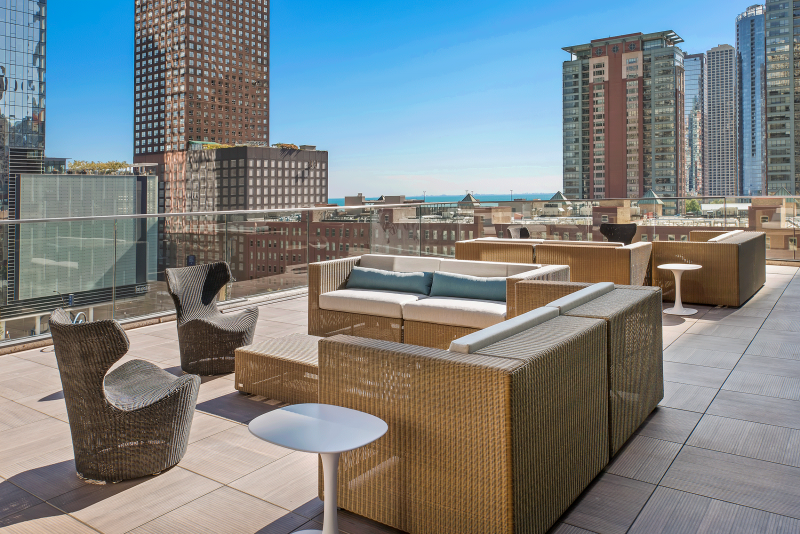 Modern rooftop deck with city views of Chicago, glass railings, and brown wicker patio furniture