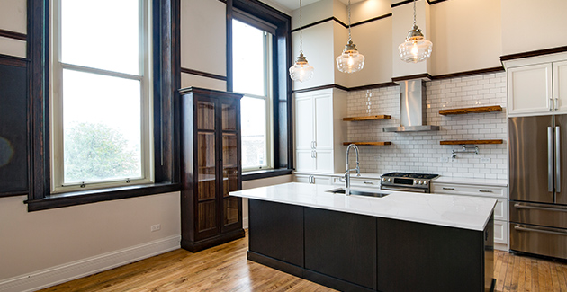 kitchen with white subway tile backsplash and custom kitchen island in converted elementary school that now houses loft apartments in Chicago