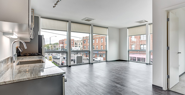 Kitchen and living area in front of floor-to-ceiling glass windows in Logan Square apartments for rent