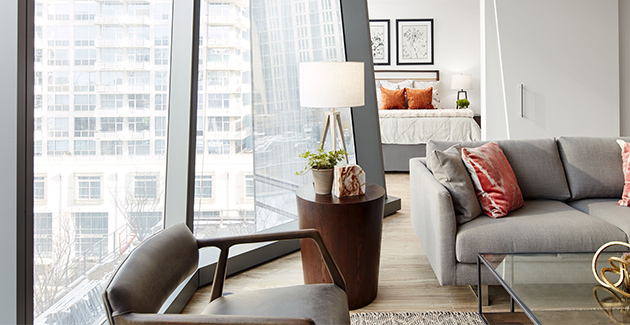 living room and bedroom divided by angled glass window in The Paragon Apartments for rent in the South Loop, Chicago