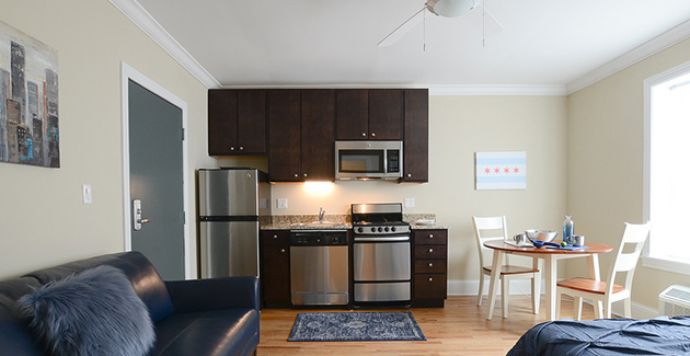studio apartment with stainless steel kitchen appliances, dark wood cabinets and breakfast nook in Rogers Park, Chicago, IL