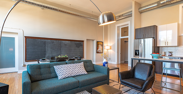 living room of loft apartment for rent in Stewart School Lofts with chalkboard in background, Chicago