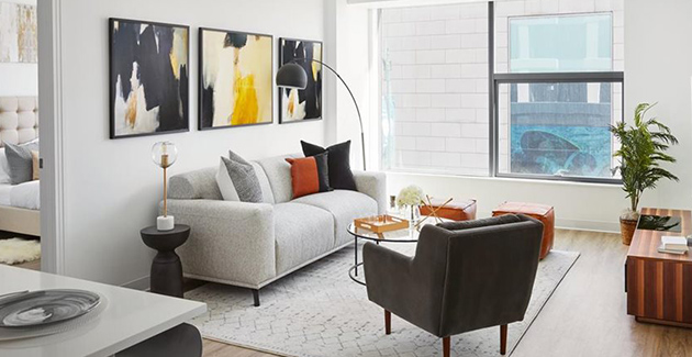 living room with modern artwork hanging on white walls and grey sofa in West Loop apartment for rent at The Van Buren