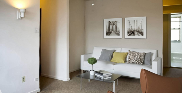 white sofa and leather armchair in studio apartment for rent in Edgewater, Chicago