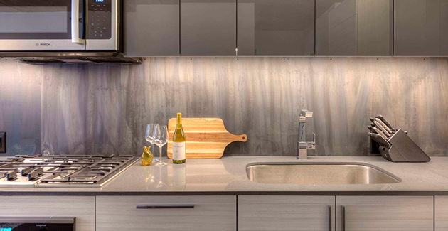 kitchen backsplash and chrome plated faucet next to stainless steel appliances in apartment for rent at Xavier in Chicago