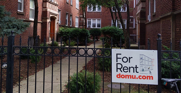 brick apartment building courtyard with For Rent sign posted at front gate in Chicago