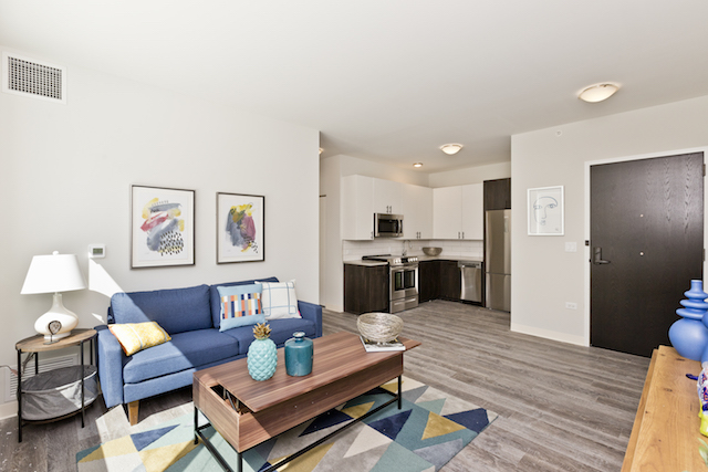 living room with blue sofa and wooden coffee table in Edgewater apartment for rent