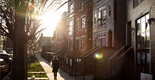 a woman walks her dog in front of apartments and townhomes in Humboldt Park neighborhood, Chicago, IL