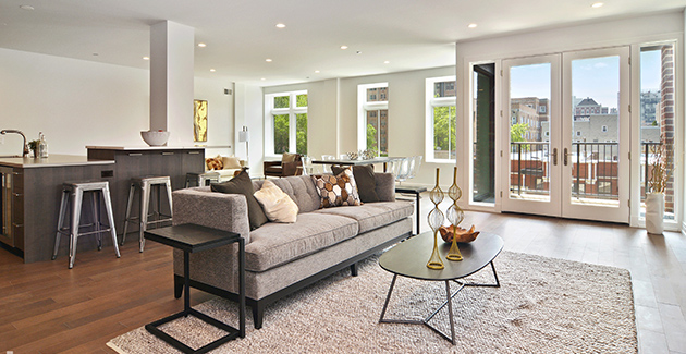 grey sofa and oval-shaped coffee table on a beige rug in luxury apartment for rent in Lakeview, Chicago