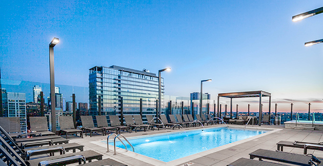 rooftop pool of luxury apartment building with lounge chairs and lighting photographed at sundown in Chicago