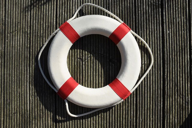 a white and red lifesaver ring hanging on a corrugated steel wall