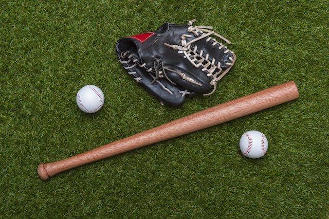 baseballs and baseball bat lying on grass beside black leather baseball mitt