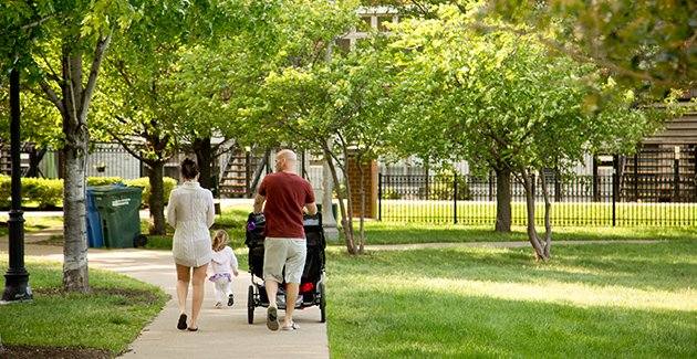 parents strolling with child in a park in the South Loop neighborhood of Chicago, IL