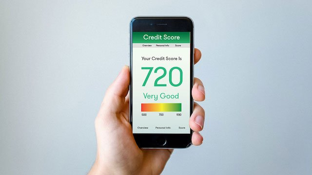 person holding a smartphone displaying a very good credit score of 720 on its screen