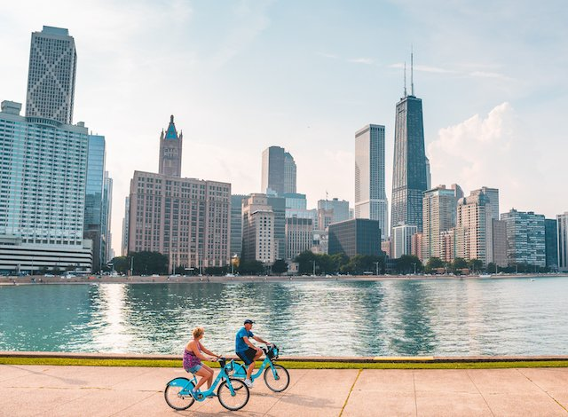 cyclists ride Divvy Bikes on Navy Pier with Chicago downtown skyline and Lake Michigan in background