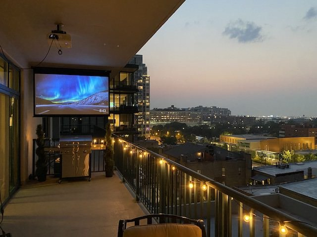 Chicago apartment balcony with projector screen and BBQ grill