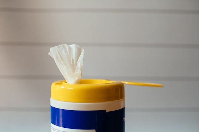 yellow lid with disinfectant wipe sticking out of container
