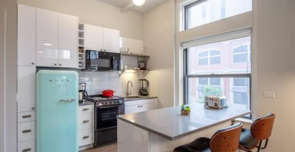 a kitchen with an aqua colored fridge and breakfast bar in a furnished apartment for rent in Chicago
